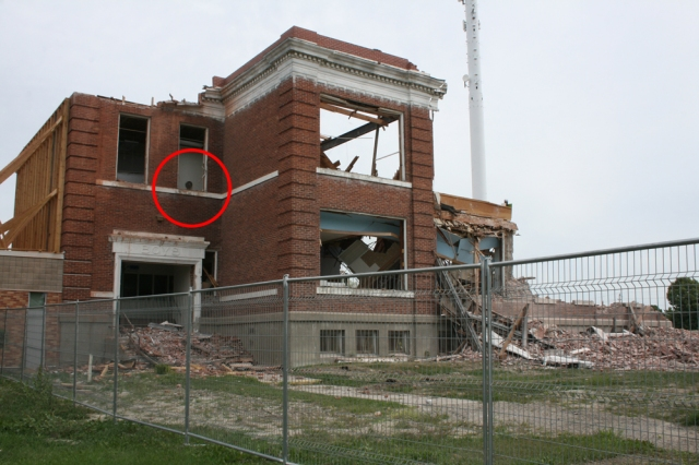 Picture of an old brick school being torn down, with a dark blob in one of the upstairs windows that kind of appears to be a head looking out.