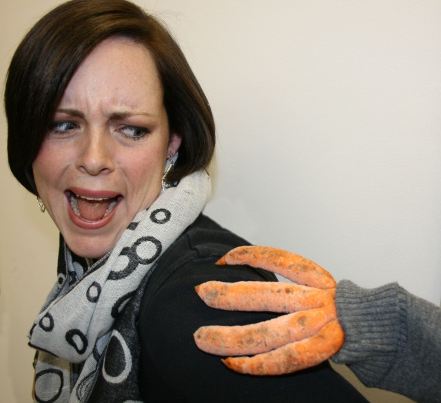 Woman screaming as a carrot that looks like a hand rests on her shoulder