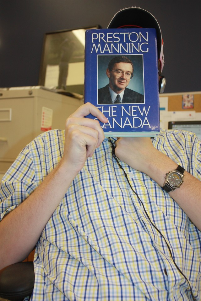 "Sports reporter holding up Preston Manning's book ""The New Canada"""