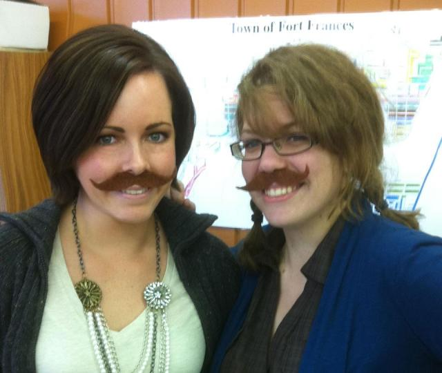 Two awesome girls wearing felt mustaches