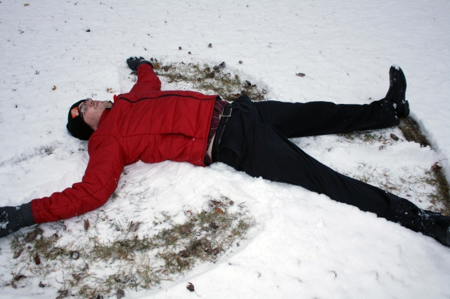 Extremely tall and gangly sports reporter making a snow angel